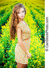 yellow blooming - Beautiful girl standing in a field of...
