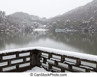 Snowfall on the lake in a beautiful Japanese garden in Kyoto