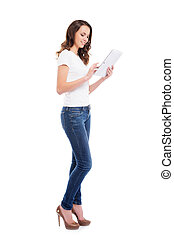A young and happy girl in stylish jeans holding a tablet...