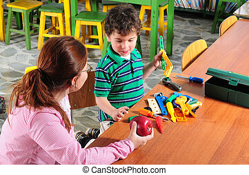 Preschool - Student in a library with his teacher