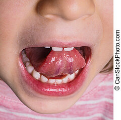 Little girl with pink shirt protruding tongue backwards with...