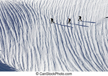 three climbers crossing a snowfield in the Pyrenees