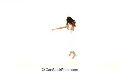 Slim woman in light dress dancing contemp jazz modern, do the splits on white background