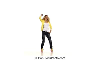 Young blond girl in yellow shirt dancing sexy-jazz modern style on white background, slow motion
