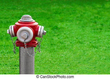 Modern red hydrant on a green grass