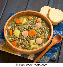 Lentil Soup - Wooden bowl of lentil soup made with potato,...