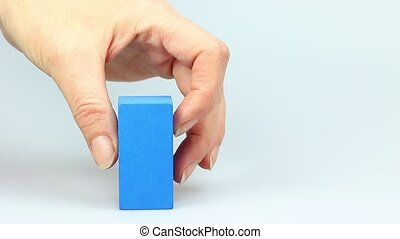Wooden cubes decrease concept - Womans hand is building blue...