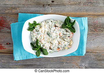 Simple Olivier Salad on old picnic table garnished with mint