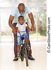 african man helping his son to ride a bike