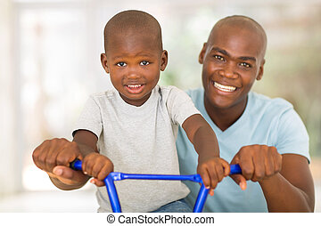 african man helping son to ride a bicycle