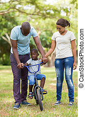 young parents teaching their son to ride a bicycle