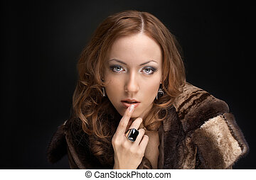Riches - Expensively dressed beautiful woman on a black...