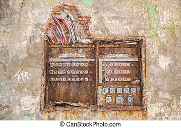 old rusty fuse box with broken dangerous wires above