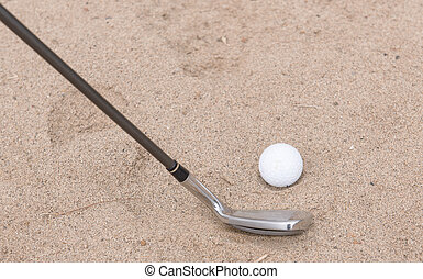 Golf ball falling into the sand trap.