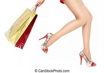 Hasten in shop - Beautiful legs of the running woman holding...