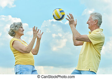 couple playing volleyball - elderly couple playing...