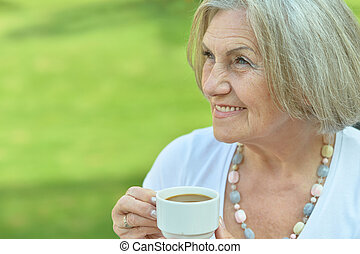 Happy elderly woman with cup of coffee