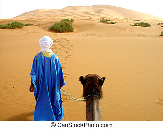 Traditional arab man walking through the desert with a camel...