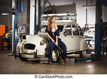 Young sexy woman repairing the retro car