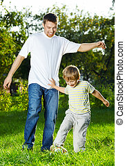 Competition to daddy - Father and small son play a ball in...