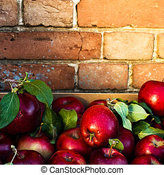 Red Apples with green leaves on rustic old background....