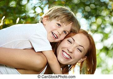 Fun - Small son piggyback on mother in a summer garden