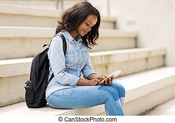 young college student using smart phone - beautiful young...