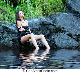 Young and beautiful girl in bikini taking bath in a...