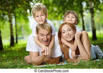 Family on a lawn - Happy family with two sons frolic on a...