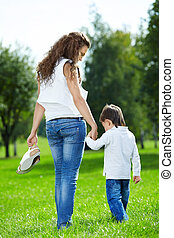 Barefooted walk on a grass - Mother with the small son...