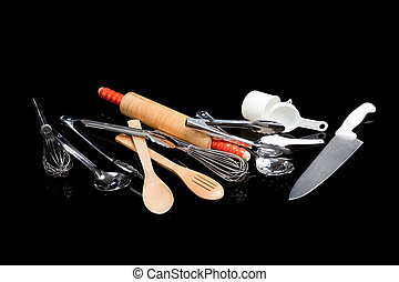 Assorted cooking utensils on black