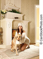 Attractive woman with the dog near the fireplace