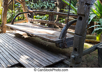 old wooden swing in the garden - sunlight on old wooden...