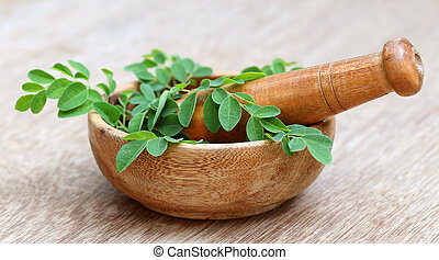 Moringa leaves and mortar pestle - Moringa leaves with...