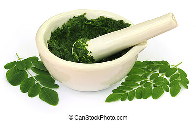 Moringa leaves with mortar and pestle over white background