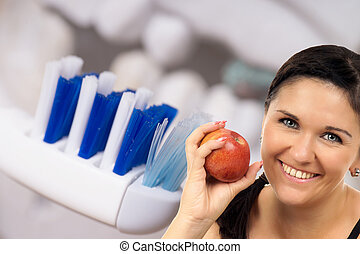 Dental Health - young woman with apple in front of a denture...