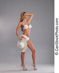 Young, slim, healthy and beautiful woman in swimsuit over...