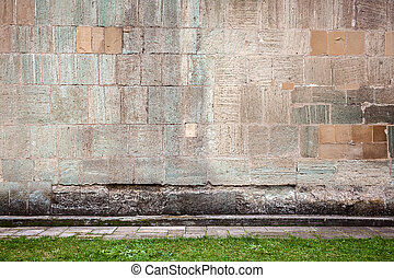 Wall of stone blocks and a pavement