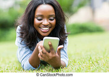 young african american woman using smart phone - cheerful...