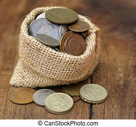 Old coins in sack bag on wooden surface