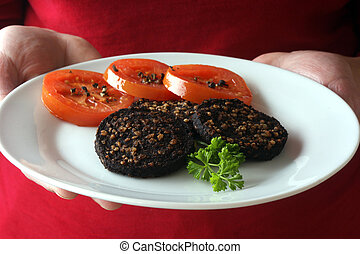 black pudding on a white plate with parsley