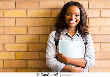 african american college girl leaning against a wall - happy...