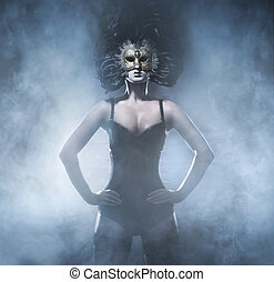 Young attractive woman in mask over dark background