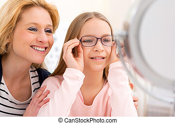 Young little girl trying glasses at the optician w her...