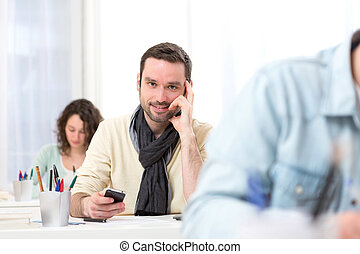 Young attractive student using his mobile during classes -...