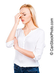 Bad feelings. Depressed mature women touching her head and keeping eyes closed while standing against white background