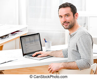Young smiling man in front of a computer - View of a Young...
