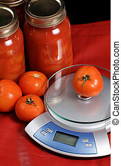 Canned Tomatoes and a kitchen scale shot against a red...