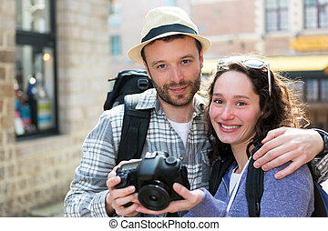 Young couple of tourist watching photographs on camera -...