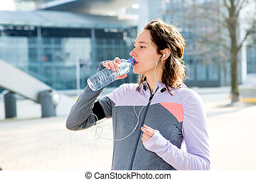 Woman drinking water during a running session - View of a...